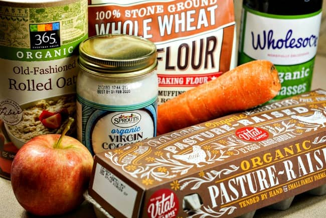 Ingredients to make apple carrot dog treats. Eggs, coconut oil, apple, carrot, molasses, rolled oats, whole wheat flour