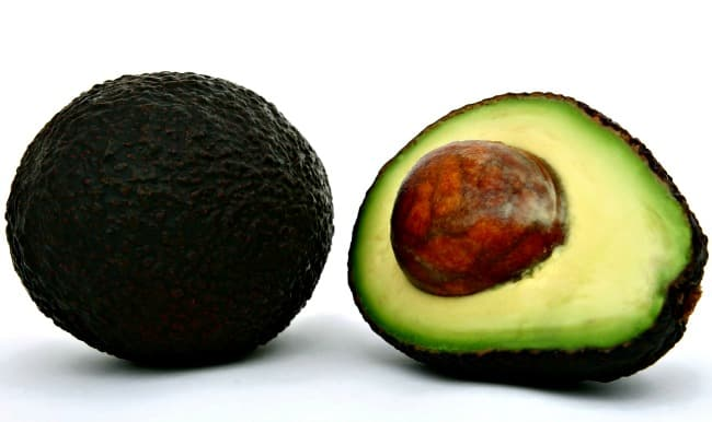 An avocado sliced in two showing flesh, pit and skin