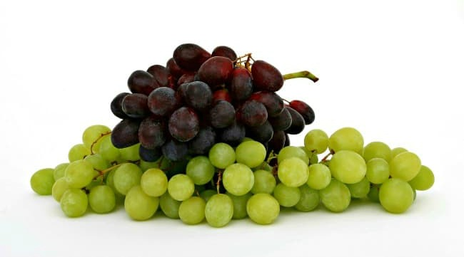 A bunch of green grapes, with a bunch of red grapes on top of them