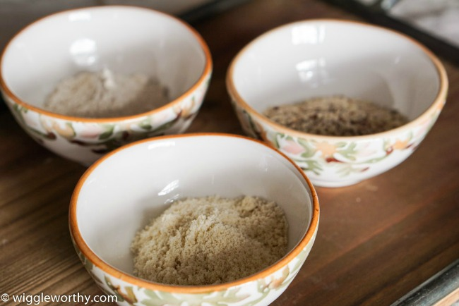 Oat flour, blanched almond flour and almond meal, in small bowls on wooden tray