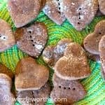 Heart shaped peanut butter and carob dog treats on green place mat